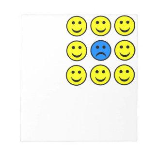 Cara sonriente triste en una muchedumbre de blocs de notas