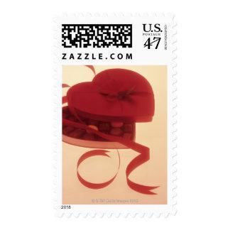 Caramelo en la caja en forma de corazón para el el sello postal