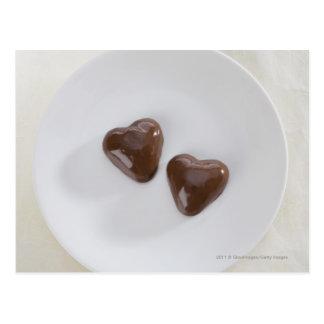 Caramelos de chocolate en forma de corazón en una  tarjetas postales