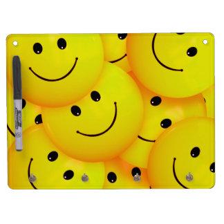 Caras sonrientes amarillas felices frescas de la tableros blancos