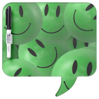 Caras sonrientes verdes felices frescas de la tablero blanco