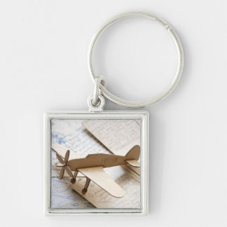 Carboard airplane on postcards keychain