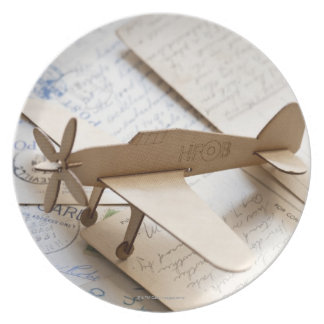 Carboard airplane on postcards plate