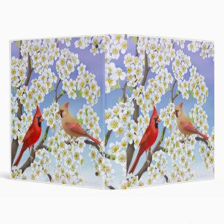 Cardenales en carpeta del árbol floreciente
