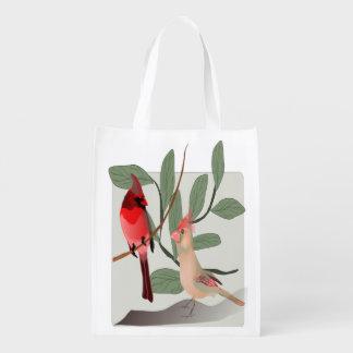 Cardenales rojos con las ramas, pájaros del bolsas reutilizables