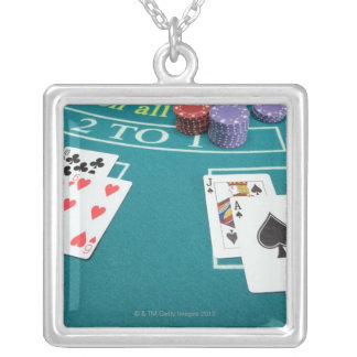 Cards and chips on betting table silver plated necklace