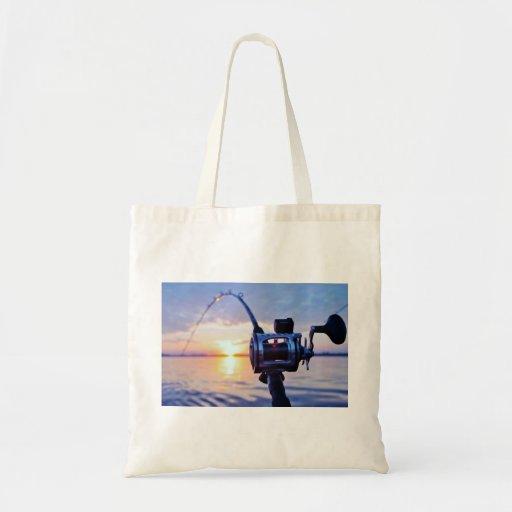 Carrete de la pesca en la puesta del sol bolsas