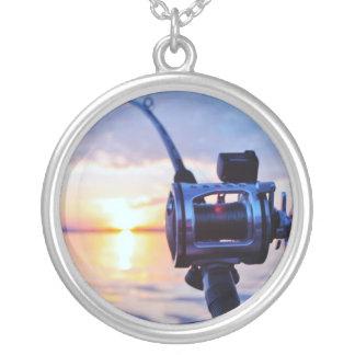 Carrete de la pesca en la puesta del sol pendientes