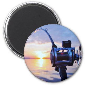 Carrete de la pesca en la puesta del sol imán de nevera
