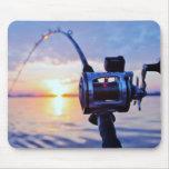 Carrete de la pesca en la puesta del sol alfombrillas de raton