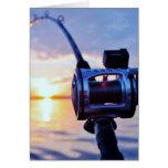 Carrete de la pesca en la puesta del sol tarjetas