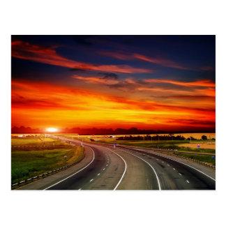 Carretera americana en la puesta del sol postales