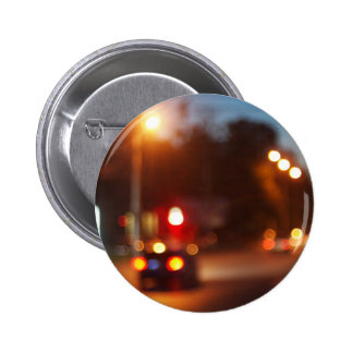 Cars with headlights on driving on city road 2 inch round button