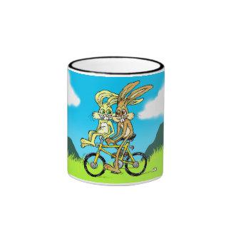 Cartoon of two bunnies on a bicycle, on a mug. ringer mug