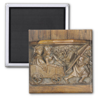 Carving depicting a couple in cart pulled by a 2 inch square magnet