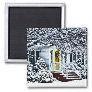 Casa con la puerta amarilla en invierno imán cuadrado