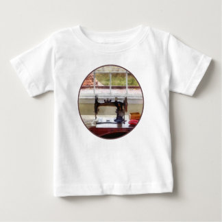 Casa de la granja con la máquina de coser tee shirts