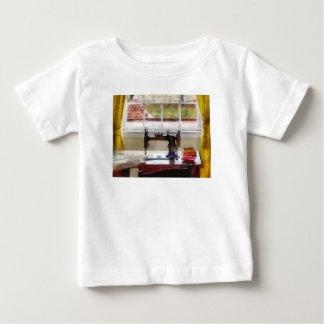 Casa de la granja con la máquina de coser t-shirt