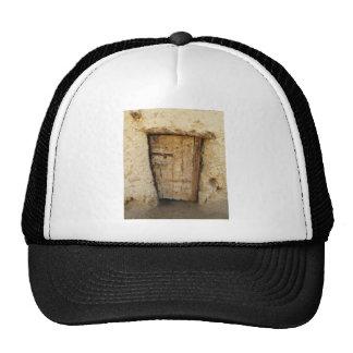 Casa del ladrillo del fango con el oasis viejo de  gorro de camionero