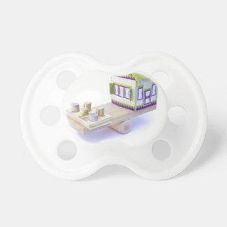 Casa en equilibrio con la pila de monedas y de chupete de bebé