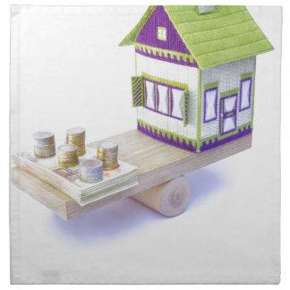 Casa en equilibrio con la pila de monedas y de servilleta de papel