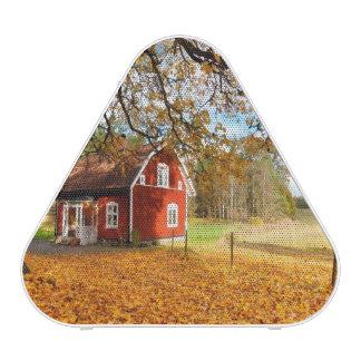 Casa sueca roja entre las hojas de otoño altavoz