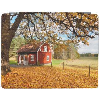 Casa sueca roja entre las hojas de otoño cubierta de iPad