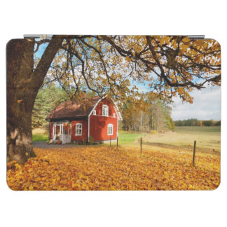 Casa sueca roja entre las hojas de otoño cubierta de iPad air
