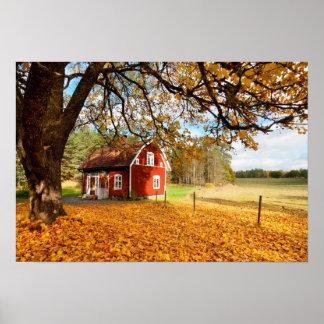 Casa sueca roja entre las hojas de otoño póster