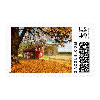 Casa sueca roja entre las hojas de otoño timbres postales