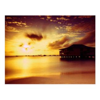 Casa y orilla en la puesta del sol postal