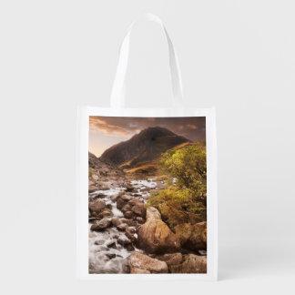 Cascada en montañas con dramático cambiante bolsa de la compra