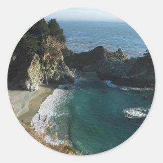 Cascada sobre la playa que fluye en el océano en pegatina redonda
