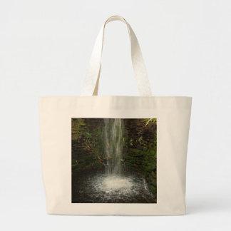 Cascada sobre piedras cubiertas de musgo bolsas