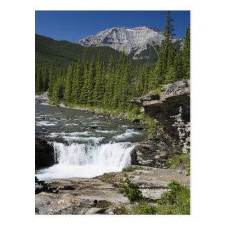 Cascadas con la repisa de la roca y una montaña tarjeta postal
