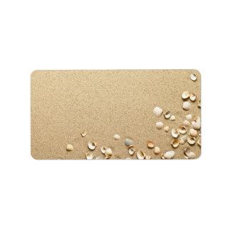 Cáscaras del mar en la arena etiqueta de dirección