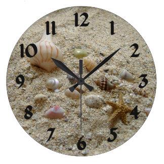 Cáscaras del mar en la arena relojes de pared