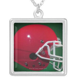 Casco de fútbol americano americano rojo en fondo collar plateado