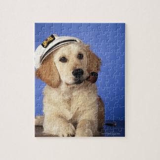 Casquillo que lleva del perro, sosteniendo el tubo rompecabeza con fotos