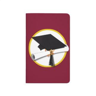 Casquillo y diploma - fondo rojo oscuro de la cuaderno grapado