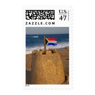 Castillo de la arena con la bandera surafricana, estampilla
