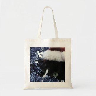 Cat in santa hat hiding in blue tinsel peering out tote bag