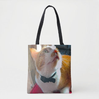 Cat on red cushion tote bag