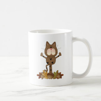 Cat playing in leaves coffee mugs