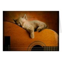Cat sleeping on guitar card