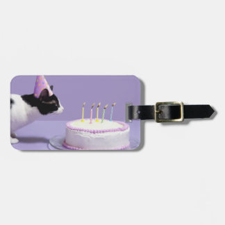 Cat wearing birthday hat blowing out candles on bag tag