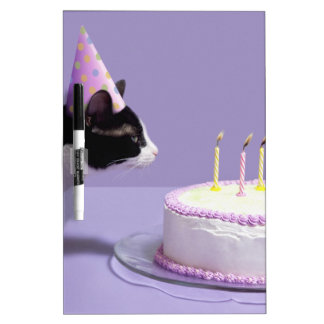 Cat wearing birthday hat blowing out candles on dry erase board