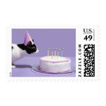 Cat wearing birthday hat blowing out candles postage