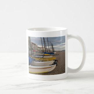 Catamaranes en la playa tazas de café