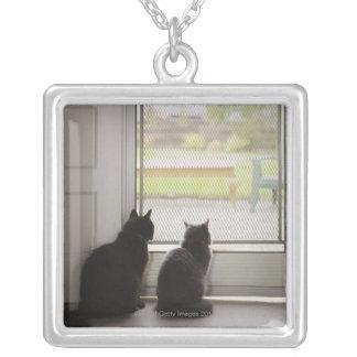 Cats looking out screen door pendant